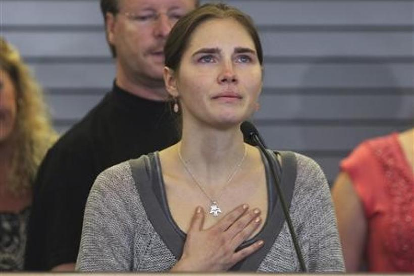 Amanda Knox pauses emotionally while speaking during a news conference at Sea-Tac International Airport, Washington after landing there on a flight from Italy