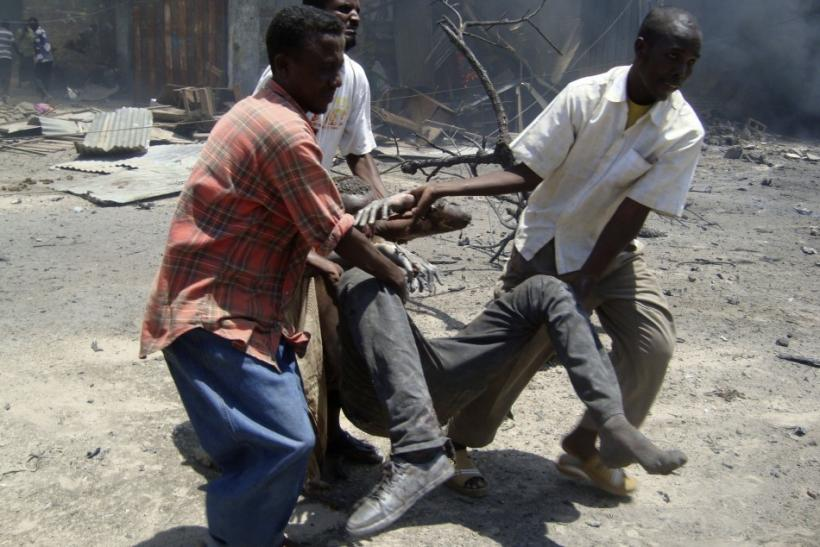 Somali soldiers carry an injured man from the scene of a suicide attack in Mogadishu Oct. 4, 2011.