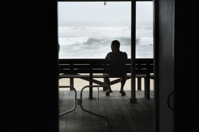 A man sits on a bench to watch waves pushed onto Long Island by the winds of Hurricane Irene in East Hampton Village, New York