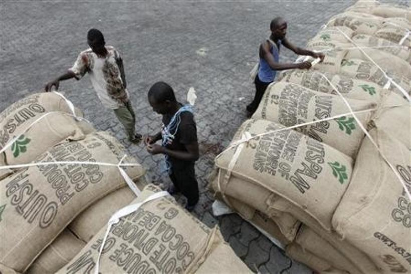 Workers prepare to load sacks of cocoa onto a ship at the port of Abidjan
