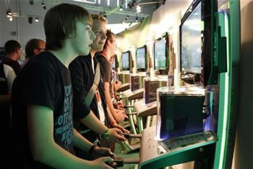 Visitors play the Xbox at the Microsoft exhibition stand during the Gamescom 2011 fair in Cologne