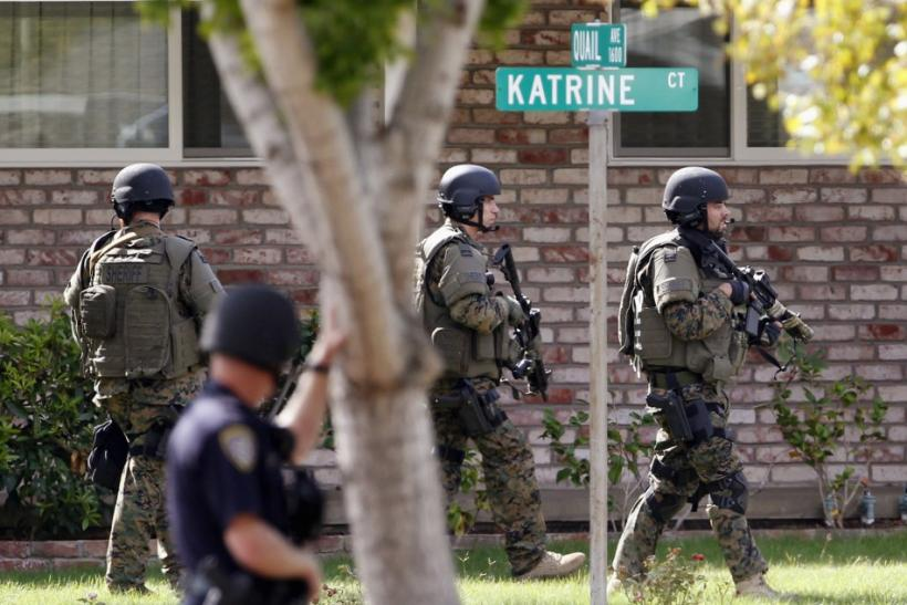 Police officers search a suburban street during a manhunt in Sunnyvale, California