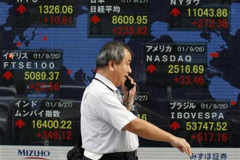 A man walks past a board showing the closing price of Japan's Nikkei share average along with other countries stock price indexes outside a brokerage in Tokyo