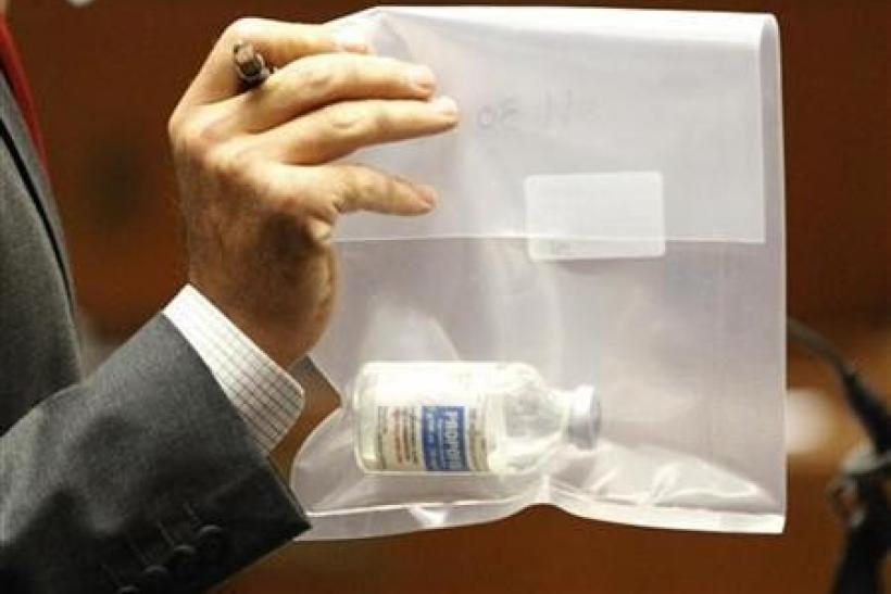 Deputy district attorney David Walgren holds a bottle of propofol found at Michael Jackson's residence during Dr.Conrad Murray's trial in the death of Jackson in Los Angeles