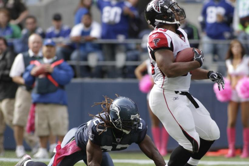 Falcons' Turner breaks free from Seahawks' Bigby and runs for a 21-yard touchdown during their NFL football game in Seattle