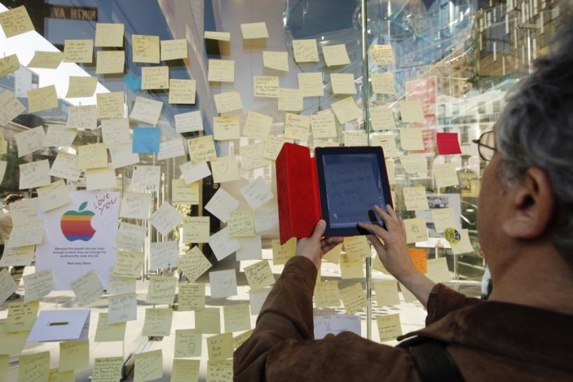 A man uses his iPad to photograph notes left memorializing Steve Jobs on the exterior of Apple's 14th St store in New York