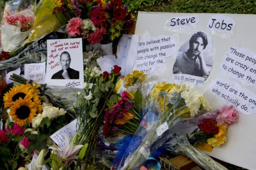 A bench outside Apple headquarters in Cupertino, California, is filled with flowers, cards and notes in honor of the passing of former Apple CEO Steve Jobs