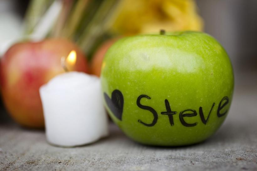 An apple with a heart and the name of Steve Jobs written on it is placed in front of a small memorial in his honour in San Francisco, California