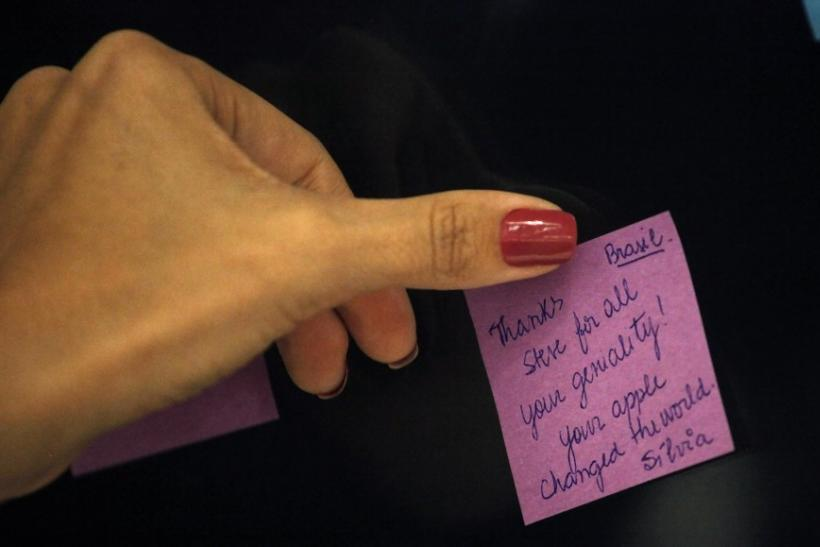 A woman adds her note next to notes by other people memorializing Steve Jobs inside of Apple's store in Sao Paulo