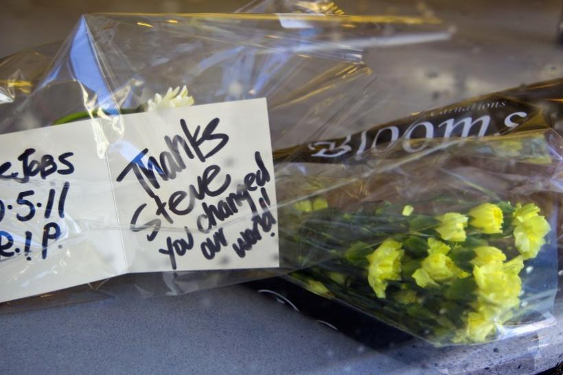 Flowers and a card in memory of Steve Jobs are seen on the floor of an Apple store in Emeryville, California