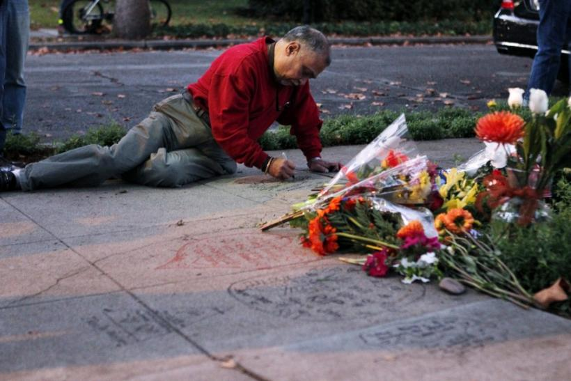"Ahmed Shafai, of Palo Alto, writes ""Steve, you made our lives easier"" on the sidewalk outside the the home of Steve Jobs in Palo Alto, California"