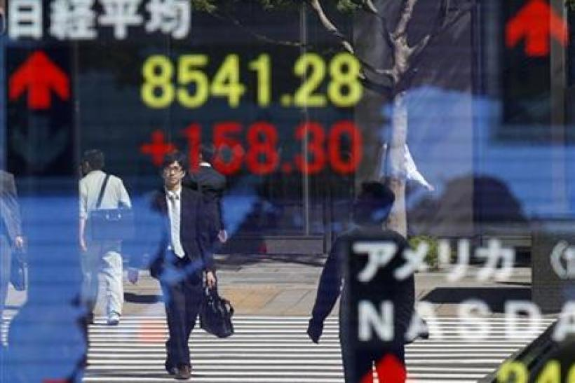 Pedestrians are reflected on a stock index board showing a current Nikkei stock average index outside a brokerage in Tokyo