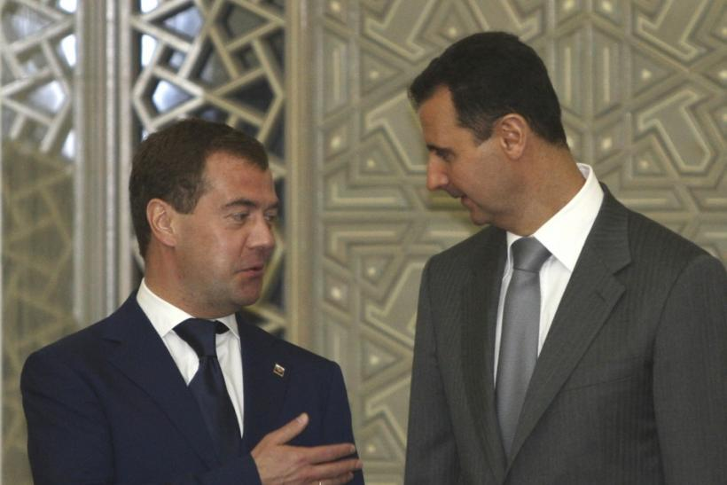 Russia's President Dmitry Medvedev chats with Syria's President Bashar al-Assad before a news conference in Damascus