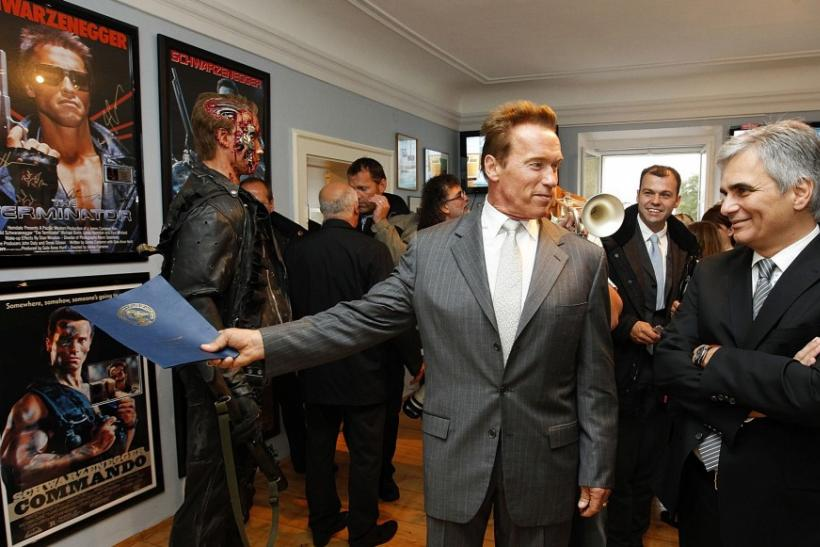 Austrian actor, former champion bodybuilder and former California governor Arnold Schwarzenegger (C) points at a 'Terminator' film poster, as he chats with Austrian Chancellor Werner Faymann, during a tour of his former home in Thal