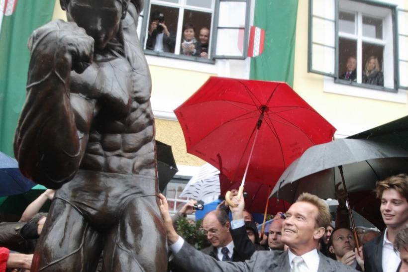 Austrian actor, former champion bodybuilder and former California governor Arnold Schwarzenegger, unveils a statue of himself in a bodybuilding pose as his son Patrick (R) watches, in Thal