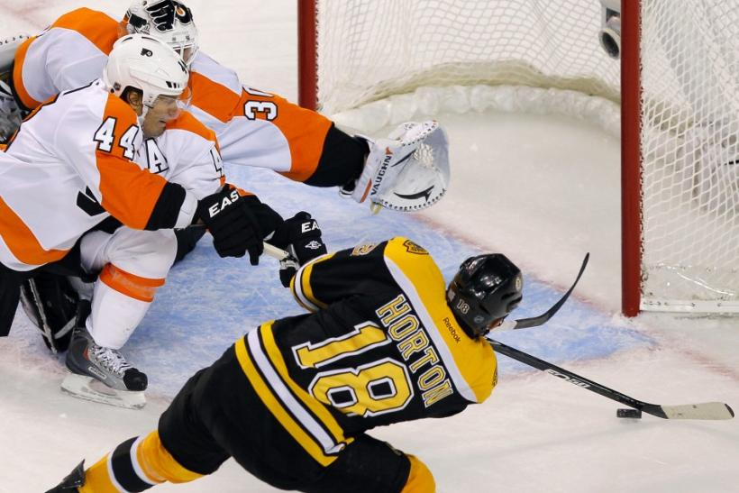 Philadelphia Flyers defenseman Kimmo Timonen makes a save on a shot by Boston Bruins right wing Nathan Horton in front of Flyers goalie Ilya Bryzgalov during the third period of their NHL hockey game in Boston