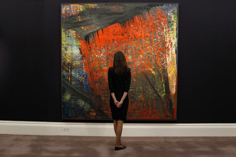 """A Sotheby's employee poses with """"Gudrun (633)"""" by Gerhard Richter from 1987 at Sotheby's in London"""