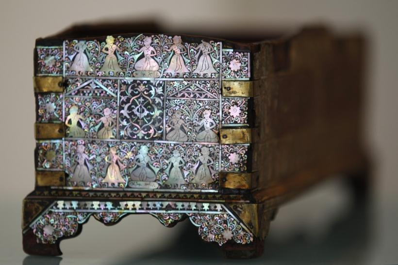 A Gujarati mother-of-pearl and black composition overlaid wooden pen box from northwest India is displayed at Christie's in Londo