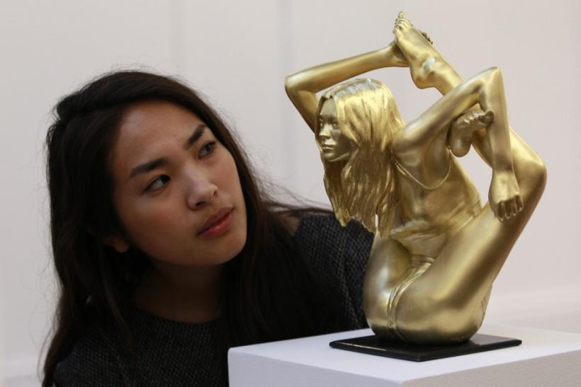 """A Sotheby's employee poses with an 18 carat gold sculpture of Kate Moss entitled """"Microcosmos (Siren)"""" by Marc Quinn"""