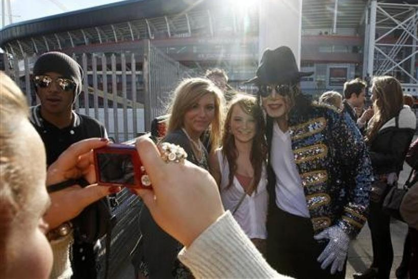 A Michael Jackson look-alike poses with fans as they queue for the ''Michael Forever'' tribute concert, which honours late pop icon Michael Jackson, at the Millennium Stadium in Cardiff, Wales