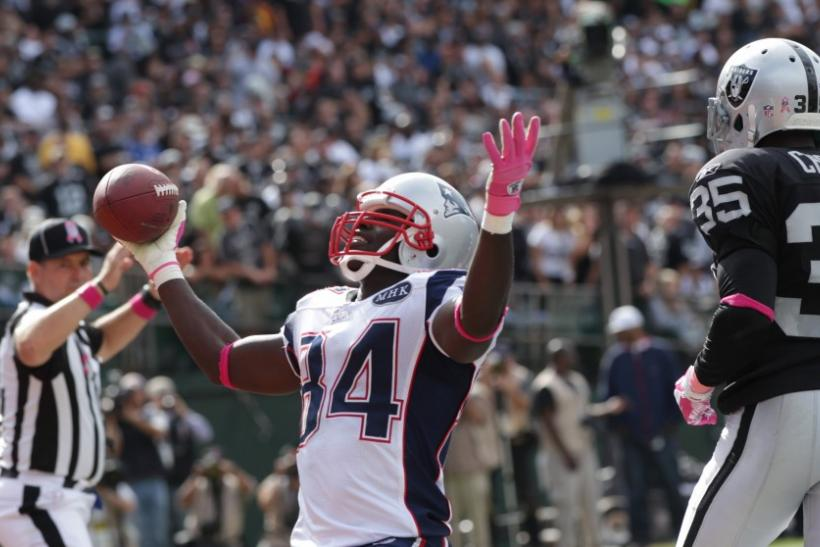 New England Patriots wide receiver Deion Branch reacts after scoring a touchdown against Oakland Raiders' Chimdi Chekwa in Oakland