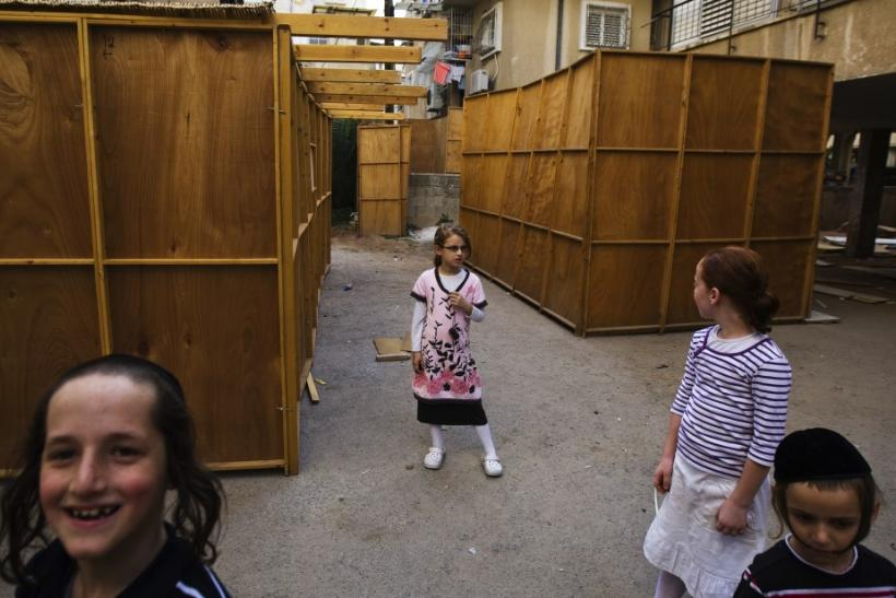 Ultra-Orthodox Jewish children play next to ritual booths known as sukkah in Bnei Brak near Tel Aviv