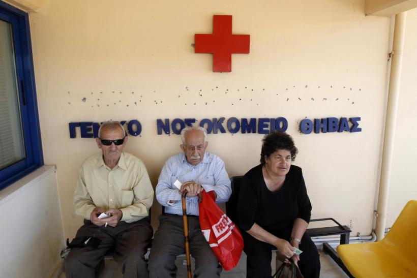 Local residents sit outside of the town's hospital in the town of Thebes, about 88 km (55 miles) northwest of Athens,