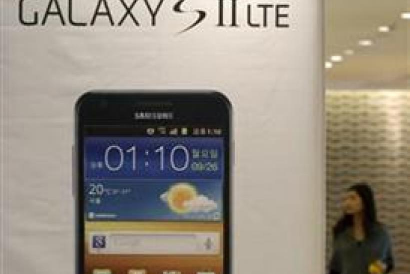 A woman walks past a billboard of Samsung Electronics' smart phone Galaxy S II LTE at the company's headquarters in Seoul