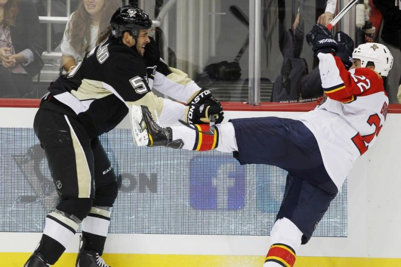 Penguins' Engelland shoves Panthers' Bradley off his skates in the third period of their NHL hockey game in Pittsburgh