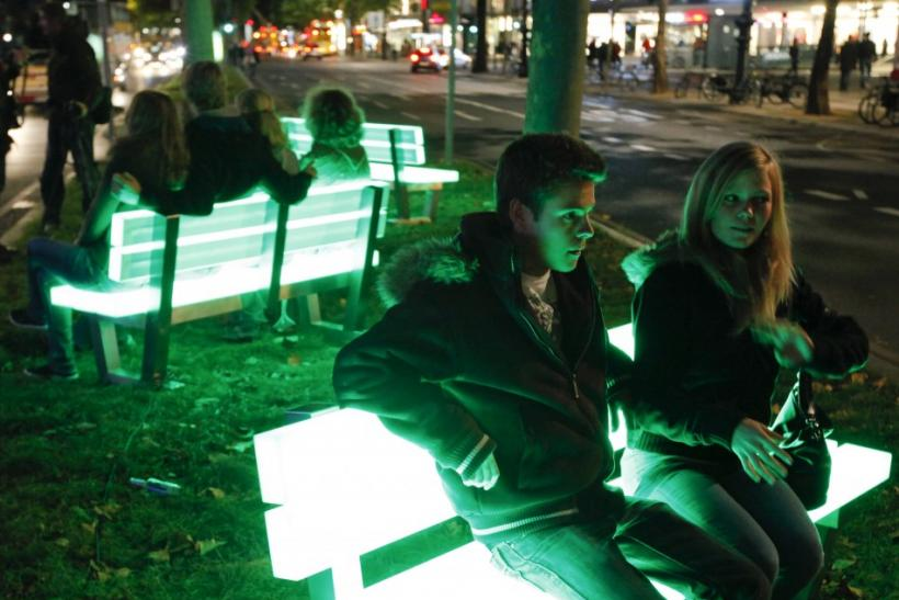 People sit on illuminated bench at the Kurfuerstendamm Boulevard during the Festival of Lights in Berlin