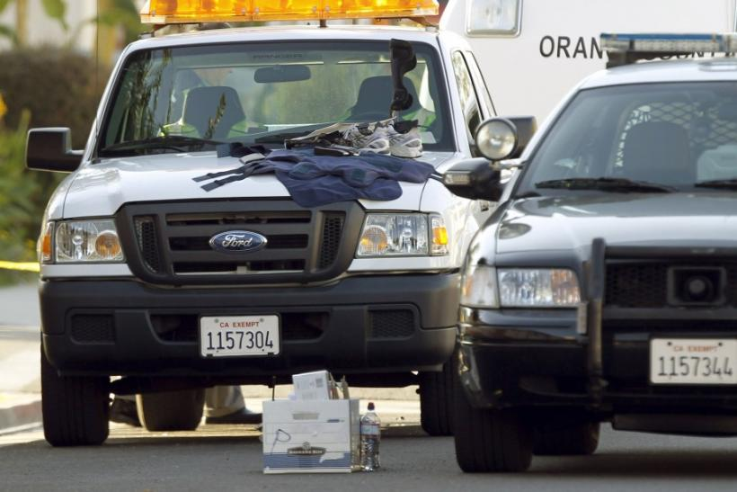 A bullet proof vest, magazines with bullets and a pair of sneakers lie on top of a police vehicle, near a white SUV that a suspect was arrested in in Seal Beach