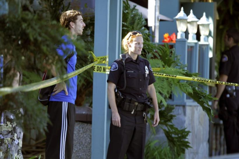 Police officer and bystander stand near police tape near Salon Meritage following a shooting that left six people dead and three injured in Seal Beach