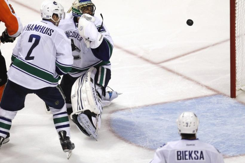 Vancouver Canucks' Luongo, Hamhuis and Bieksa watch as the Philadelphia Flyers' game winning goal heads to the net during their NHL hockey game in Philadelphia