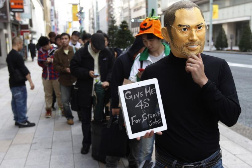 A man wearing a mask of Apple founder Steve Jobs stands in a line to buy an iPhone 4S in front of an Apple Store in Tokyo October 14, 2011.