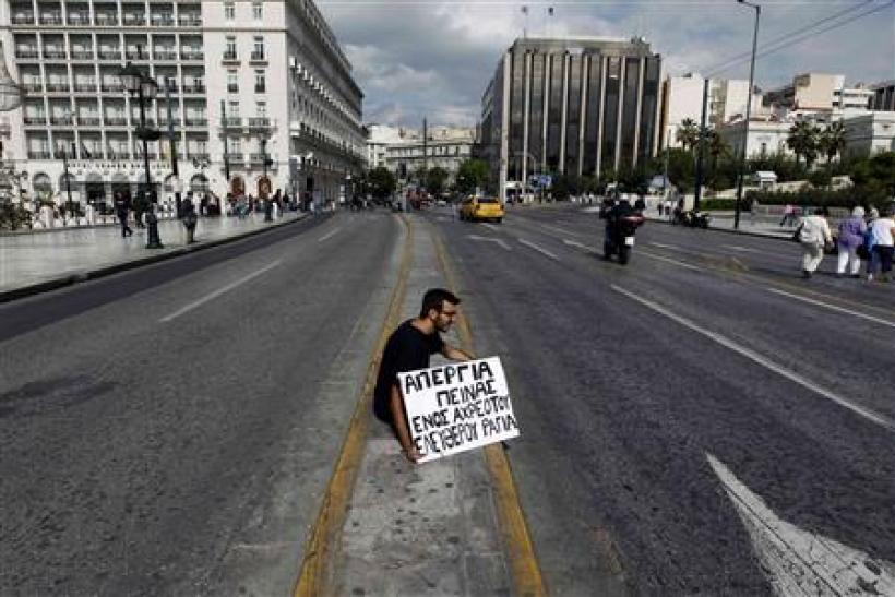 A student from Thessaloniki sits opposite the Greek parliament in central Athens with a banner