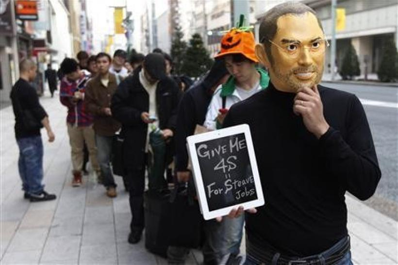 A man wearing a mask of Apple founder Steve Jobs stands in a line to buy an iPhone 4S in front of an Apple Store in Tokyo