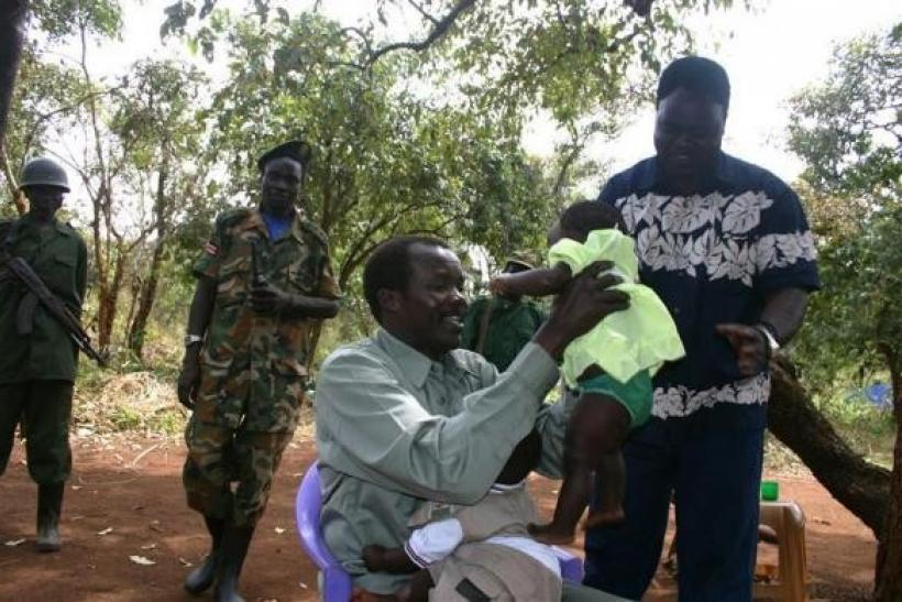 Lord's Resistance Army (LRA) leader Major General Joseph Kony, in this exclusive image, passes his daughter to LRA delegate Thomas Otim during peace negotiations between the LRA and Ugandan religious and cultural leaders in Ri-Kwangba, southern Sudan