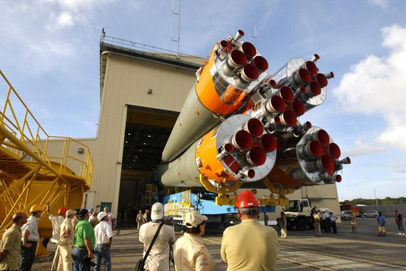 Technicians watch the Soyuz VS01 rocket as it is transported to its launch pad at the Guiana Space Center in Sinnamary, French Guiana
