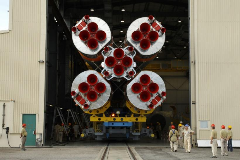Technicians stand near the Soyuz VS01 rocket as it is transported to its launch pad at the Guiana Space Center in Sinnamary, French Guiana