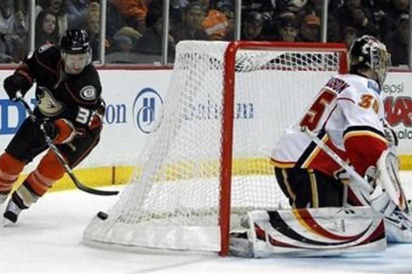 Anaheim Ducks left wing Jason Blake (33) picks up the puck off the back of the net as Calgary Flames goalie Henrik Karlsson (35), of Sweden, defends in the second period of their NHL hockey game in Anaheim, California