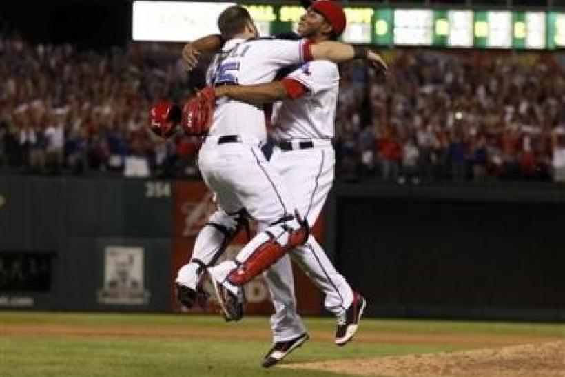 Texas Rangers relief pitcher Neftali Feliz celebrates with catcher Mike Napoli after the Rangers defeated the Detroit Tigers in Game 6 of MLB's ALCS baseball playoffs to take the pennant in Arlington