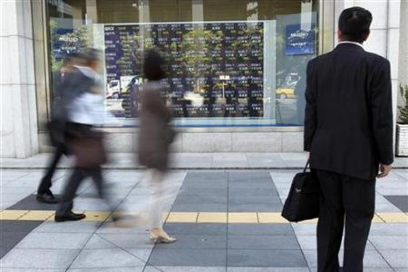 A man watches a stock index board outside a brokerage in Tokyo