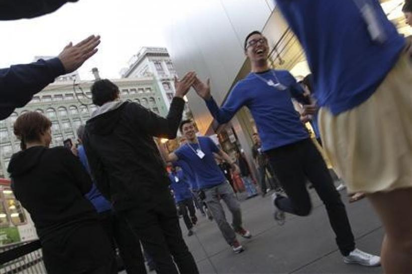 Apple employees greet customers waiting in line to purchase new iPhone 4S at Apple's flagship retail store in San Francisco, California