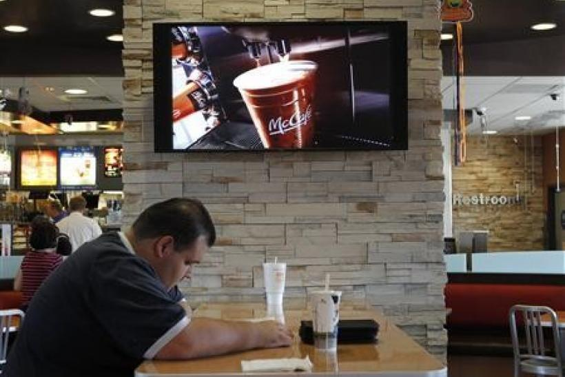 Customer Steven Price sits at a table near a HDTV screen showing the new McDonald's Channel featuring a commerical about McCafe drinks at a McDonald's restaurant, part of the test market for the channel in Norwalk, California