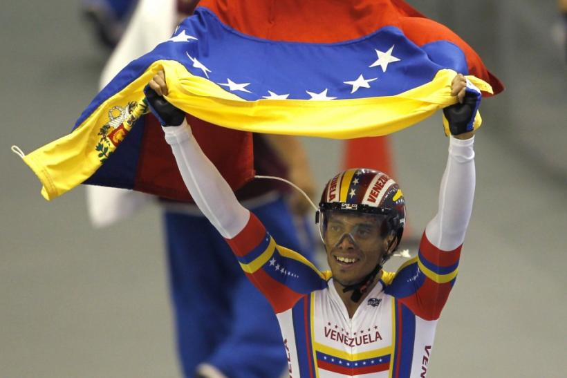 Venezuela's Cesar Marcano celebrates with his national flag after winning the gold medal in the men's team sprint cycling track competition at the Pan American Games in Guadalajara