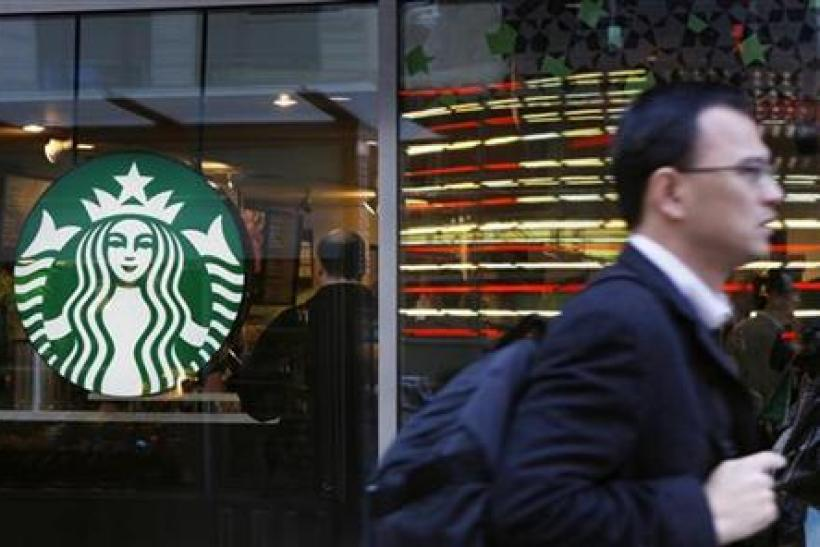 A pedestrian walks past the new Starbucks logo on a store in Times Square in New York