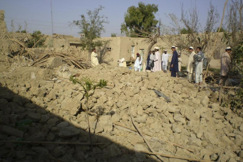 Tribesmen gather at a site of a missile attack on the outskirts of Miranshah