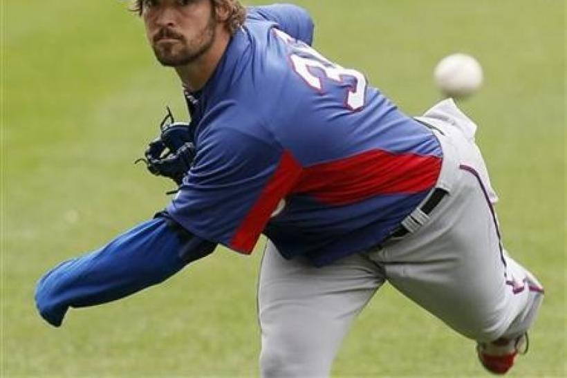 Texas Rangers starting pitcher C.J. Wilson warms-up during practice in St. Louis, Missouri