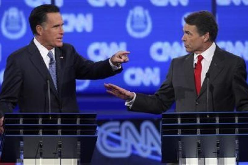 GOP presidential candidates former Massachusetts Governor Mitt Romney (L) and Texas Governor Rick Perry debate illegal immigration as they take part in the CNN Western Republican debate in Las Vegas, Nevada