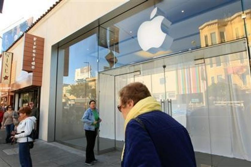 People gather outside the temporarily closed Apple retail store in the Marina District in San Francisco, California